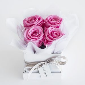 four real roses preserved to prevent ageing arranged in a small hatbox